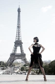 パリ、フランスのエッフェル塔の前で女の子のセクシーなダンサー。エッフェル塔のようなダンスポーズの美しい女性。ロマンチックな旅行の概念