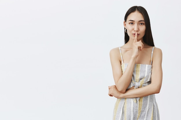 Girl sharing her secrets. portrait of charming sensual and fashionable woman in matching top and shorts, saying shh while showing shush gesture with index finger over mouth