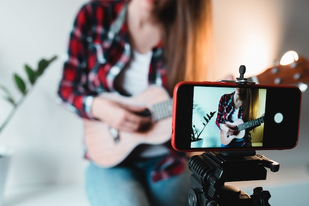 Girl in a shirt and jeans writes a vlog on the phone about playing ukulele.