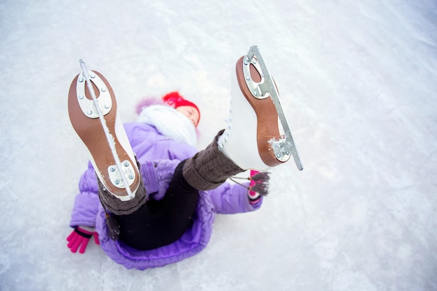 A girl, shod in figure skates, lies on the ice with her legs raised, focus on skates.