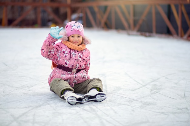 Girl shod in figure skates, sits on ice on a skating rink and waves a hand