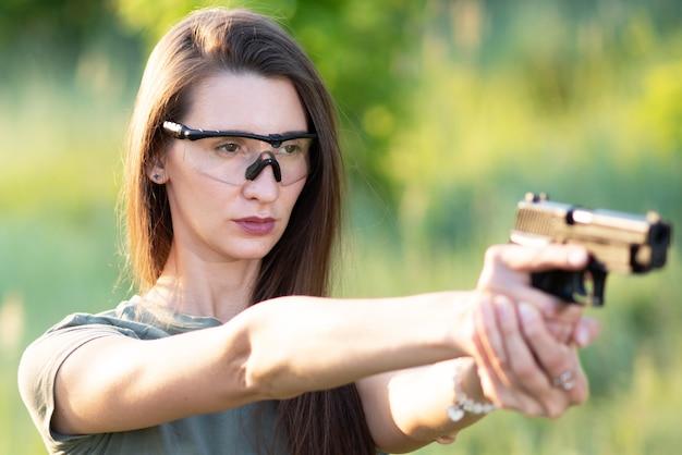 대상을 목표로 그의 손에 총을 가진 소녀 촬영 강사