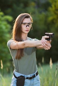 Инструктор по стрельбе девушка с ружьем в руке, целится в цель