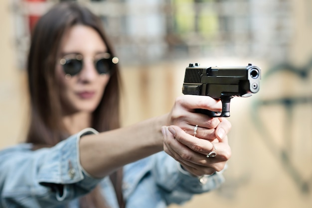 Girl shooting instructor with a gun in his hand aiming at the target