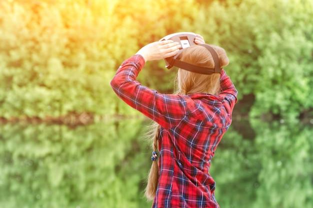 Девушка снимает очки виртуальной реальности, закат на природе, вид со спины