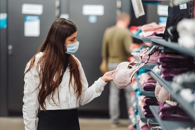 Девушка-покупатель в магазине в медицинской маске выбирает нижнее белье