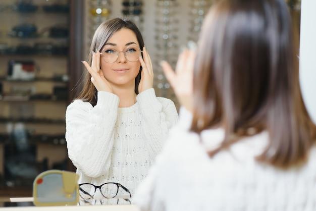 Девушка покупает очки на сезон распродаж в магазине оптики. стильный клиент покупает много очков со скидкой