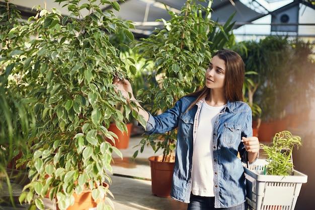 Девушка делает покупки для растений на рынке в синей рубашке.