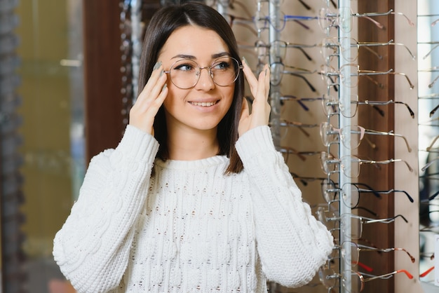 Girl shopping for glasses on sale season in optic store.