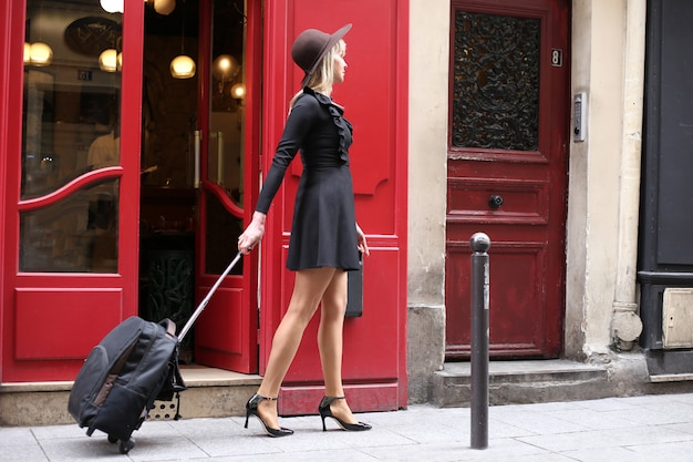 A girl in a short black dress with a hat and a suitcase is walking down the street in paris