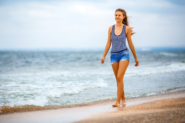 Girl in shorts walking on the beach