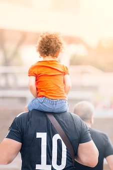 A girl on the shoulders of her father, a strong man with his partner, walks during the sunset