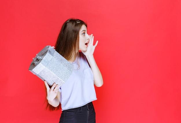 銀のギフトボックスを受け取るために誰かに叫び、電話をかけている女の子。