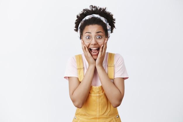 Девушка кричит от удивления. пораженная возбужденная милая афроамериканка в очках, повязке на голову и желтом комбинезоне, кричащая с отвисшей челюстью