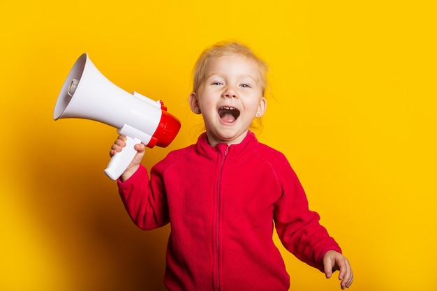 Girl shouts holding a megaphone on a bright yellow background.