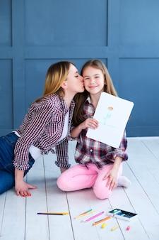 꽃의 그림을 보여주는 소녀. 그녀의 딸 키스 자랑 어머니