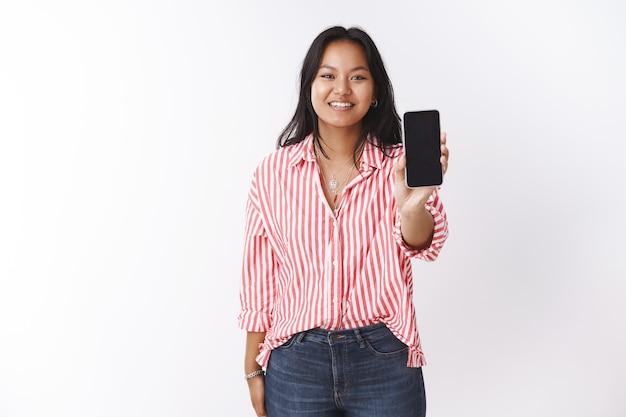 友達にアプリを見せている女の子が写真を編集していたのかと尋ねました。カメラに向かってスマートフォンを引っ張って、白い背景の上のカメラで広く笑って魅力的でかわいい若いアジアの女性の肖像画