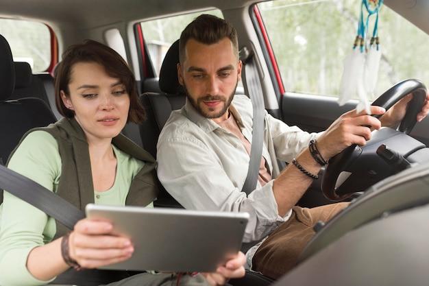 Girl showing boyfriend tablet in car