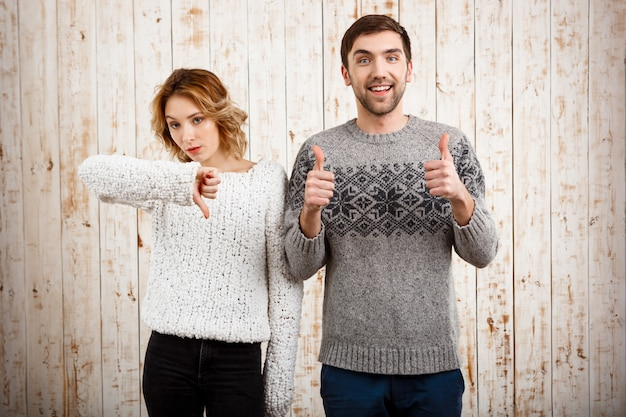 Girl showing dislike man with thumbs up over wooden wall
