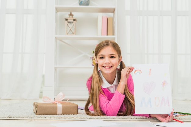 Girl showing drawing with i love mom inscription