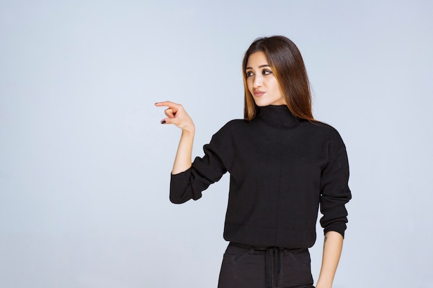 Girl showing the estimated measures of an object. high quality photo