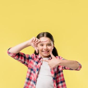 Girl showing finger frame in studio