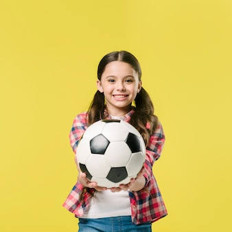 Girl showing football in studio