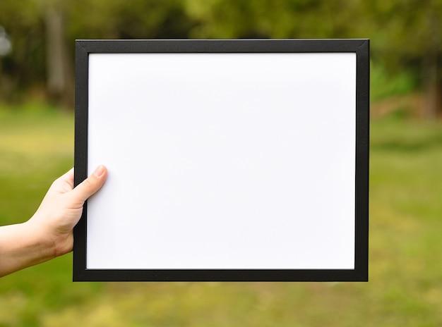 Girl showing frame mockup on bokeh background.