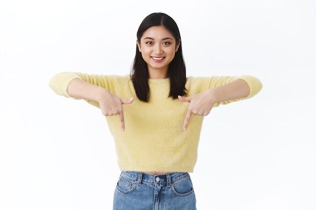 素晴らしい製品割引、素晴らしいイベントプロモーション、会社のページのバナーを表示している女の子。黄色いセーターを着た美しいアジア人女性が指を下に向けて笑っている広告をチェックしてください