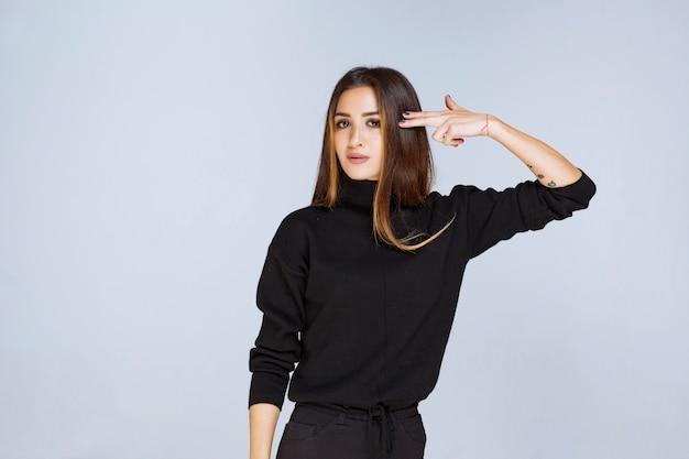 Девушка показывает пистолет знаком в руке. фото высокого качества