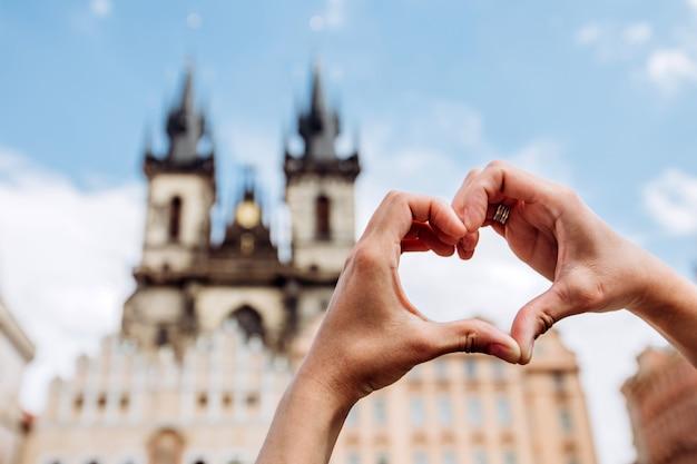 都市の景観、ティーン教会にハート形の愛のシンボルを示している女の子。手でハートを作る女性。プラハ、チェコ共和国の観光スポット