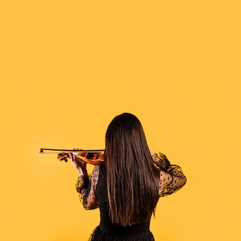Girl showing her back playing the violin