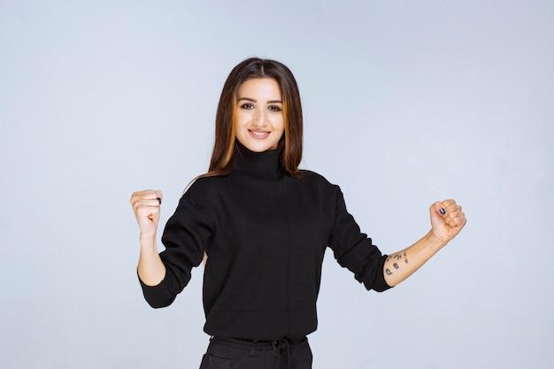 Девушка показывает свой кулак и силу. фото высокого качества