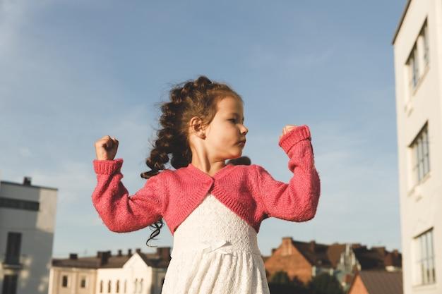 Девушка показывает мышцы на руках. на открытом воздухе летом против неба