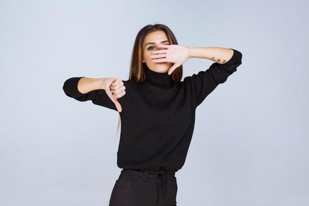 Девушка показывает отрицательный большой палец вниз знак. фото высокого качества