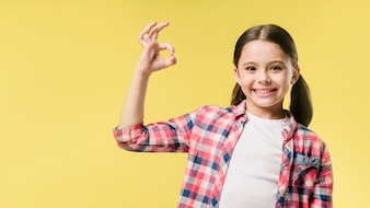 Girl showing okay sign in studio