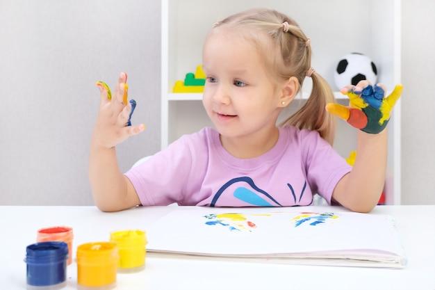 塗られた手を見せている女の子。カラフルな絵の具で描かれた手。教育、学校、芸術、絵画のコンセプト