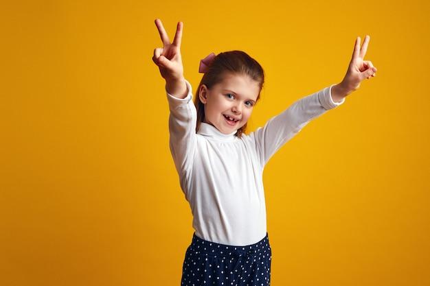Девушка показывает жест мира с поднятыми руками на желтом фоне