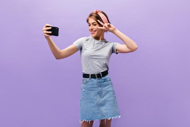 ピースサインを示している女の子、ウィンクし、紫色の背景で自分撮りをしています。ファッショナブルな衣装のポーズで素晴らしい若い女性。