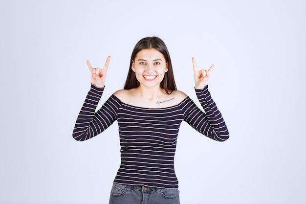 토끼 또는 늑대 귀 기호를 보여주는 소녀.