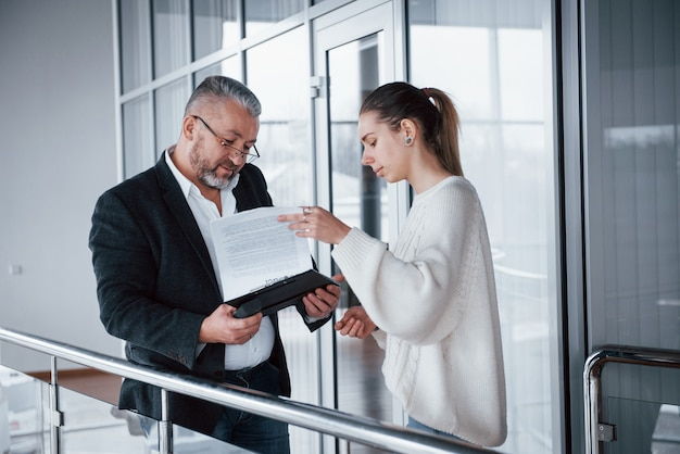 Girl showing results of work to her boss in eyewears and grey beard