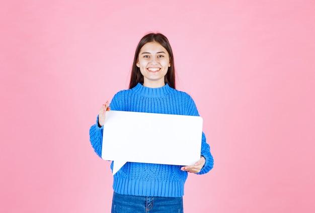 Девушка показывает знак речи пузырь баннер и выглядит счастливым на розовом.
