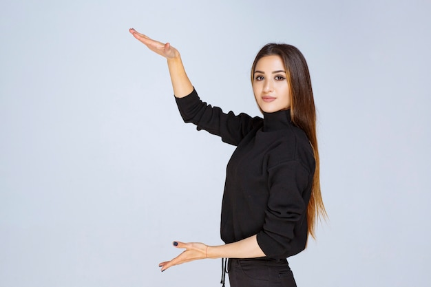 Girl showing the size of an object with hands. high quality photo