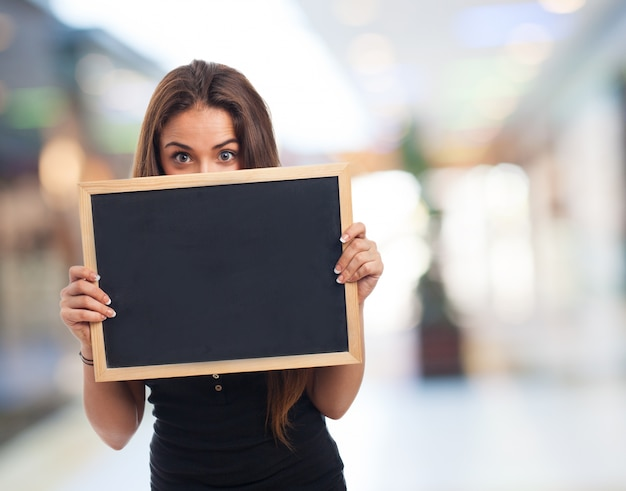 Girl showing a small blackboard with blurred background
