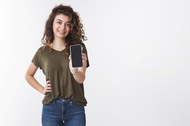 스마트폰 디스플레이 체크 아웃을 보여주는 소녀. 매력적인 사교적인 아르메니아 곱슬머리 여성이 전화를 들고 팔을 뻗고 흰색 배경에 서 있는 사진 필터에 대해 조언을 구하는 앱을 제시합니다.