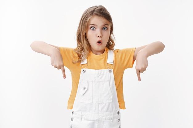 重要な何かを見せている女の子。夏のオーバーオールとtシャツに感動した興奮したかわいいかわいい子供、指を下に向け、驚いたふくれっ面、すごい驚き、白い壁に立つ