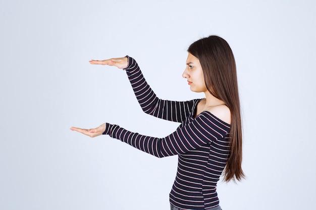 Девушка показывает количество или меры продукта.