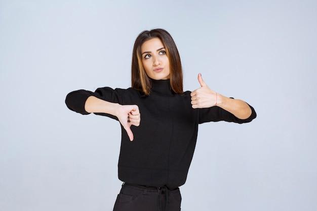 Девушка показывает палец вверх и вниз по знаку. фото высокого качества