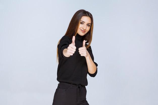 Девушка показывает палец вверх по знаку. фото высокого качества