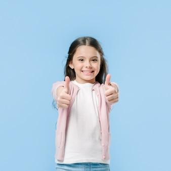 Girl showing thumbs in studio